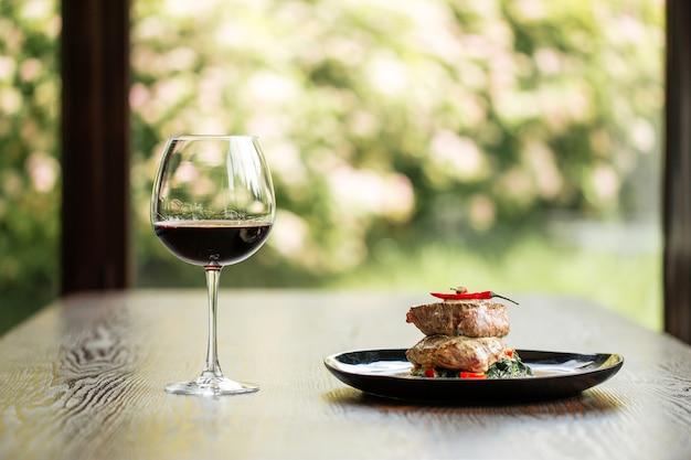 Filety mignon filetowane z sosem kieliszek czerwonego wina