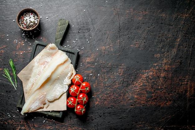 Filety rybne na papierze z nożem, rozmarynem i przyprawami w misce.
