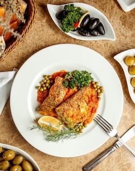 Filety rybne w sosie pomidorowym podawane z cytryną groszkiem i ziołami