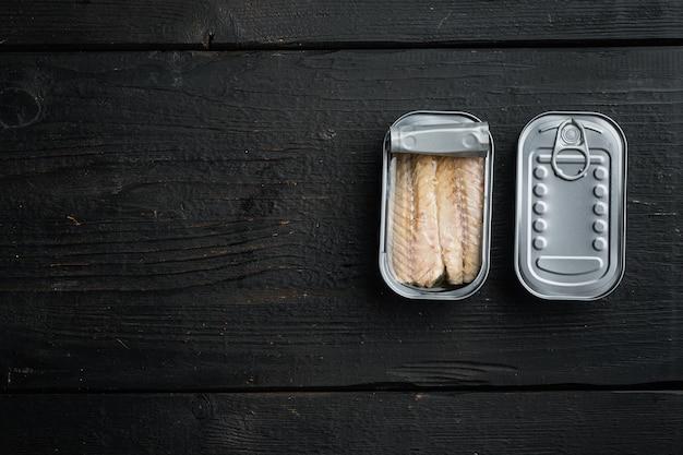 Filety z makreli w puszce w puszce na czarnym drewnianym stole