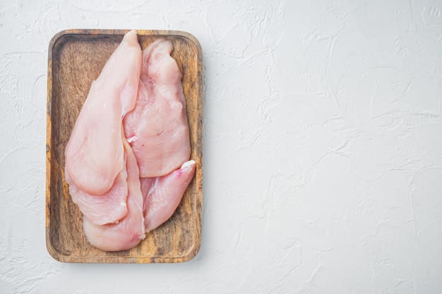 Filety z piersi kurczaka surowego, na białym tle, widok z góry płasko leżał z miejscem na tekst