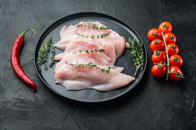 Filety z piersi kurczaka surowego, na czarnym tle