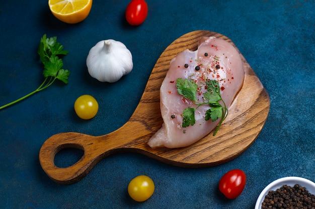 Filety z piersi kurczaka surowego na drewnianą deską do krojenia z ziołami i przyprawami. widok z góry
