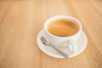 Filiżanka kawy na drewnianym stole. Napoje, motyw kawy