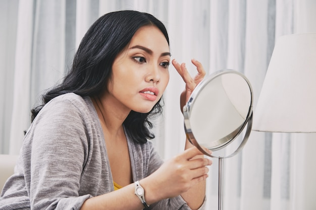 Filipińska kobieta dostosowuje makijaż
