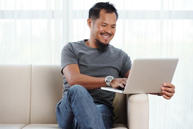 Filipiński wesoły człowiek z laptopem