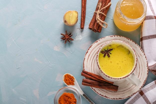 Filiżanka ajurwedyjskiego złotego kurkumy mleka latte z kurkumą, cynamonową gwiazdką anyżu