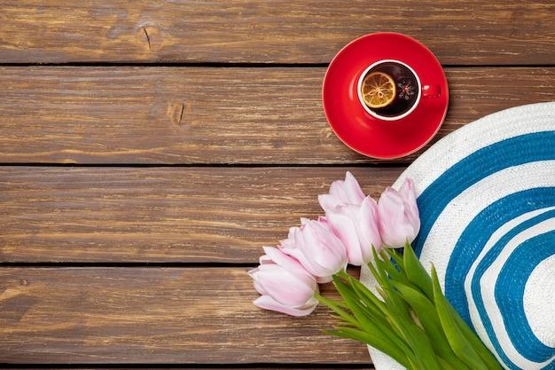 Filiżanka angielskiej herbaty z wiosennymi tulipanami i kapeluszem na drewnie