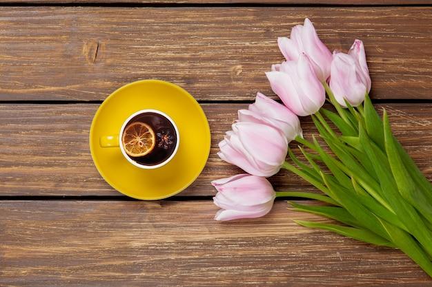 Filiżanka angielskiej herbaty z wiosennymi tulipanami na drewnie