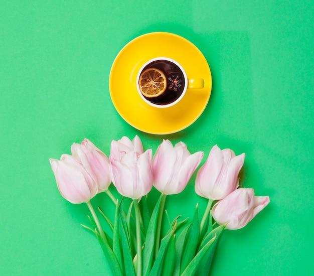 Filiżanka angielskiej herbaty z wiosennymi tulipanami na gre