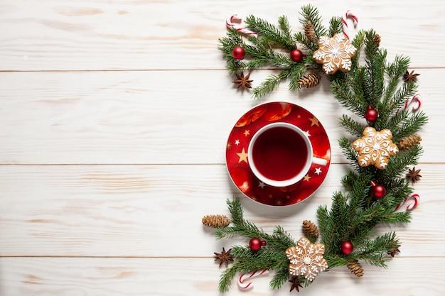 Filiżanka aromatycznej gorącej herbaty i świątecznych dekoracji z gałązkami jodły i pierniczkami