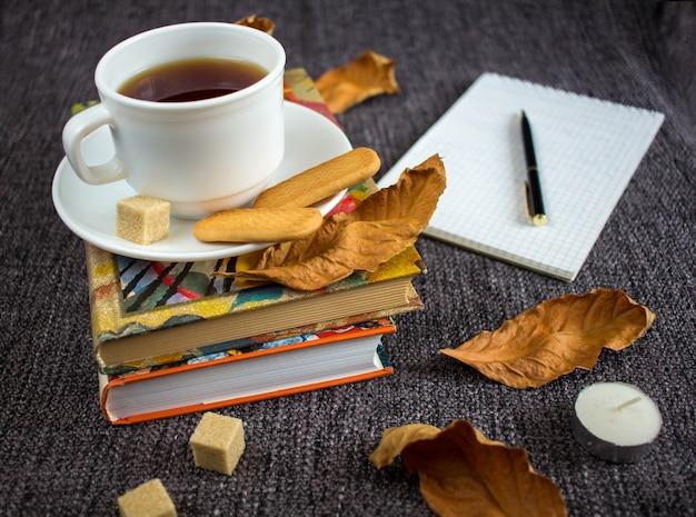 Filiżanka aromatycznej gorącej herbaty wśród żółtych liści na kratce.