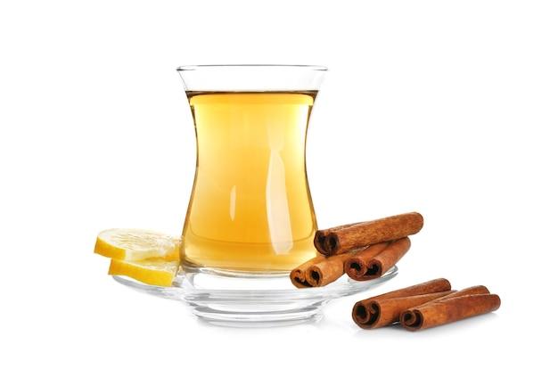 Filiżanka aromatycznej gorącej herbaty z cynamonem i cytryną na białej powierzchni