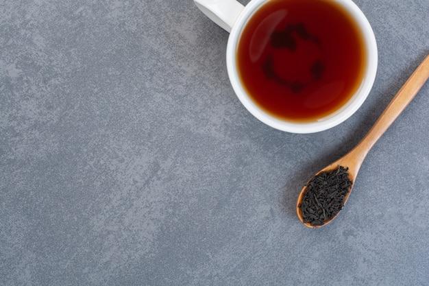 Filiżanka aromatycznej herbaty z drewnianą łyżeczką naparu.