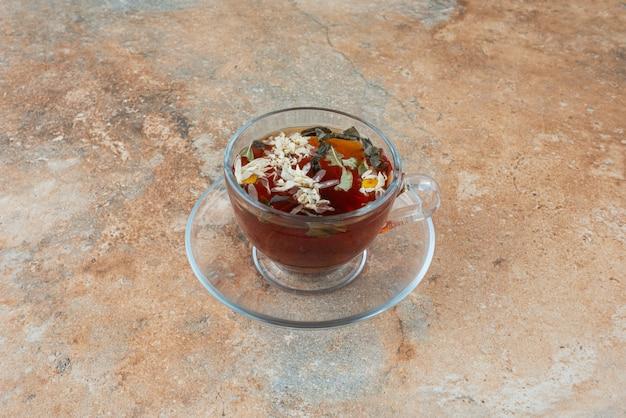 Filiżanka aromatycznej herbaty ziołowej na tle marmuru