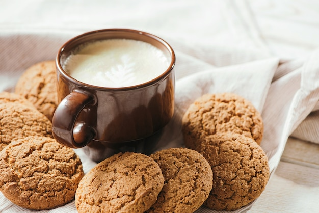 Filiżanka aromatycznej kawy cappuccino z ciasteczkami owsianymi.