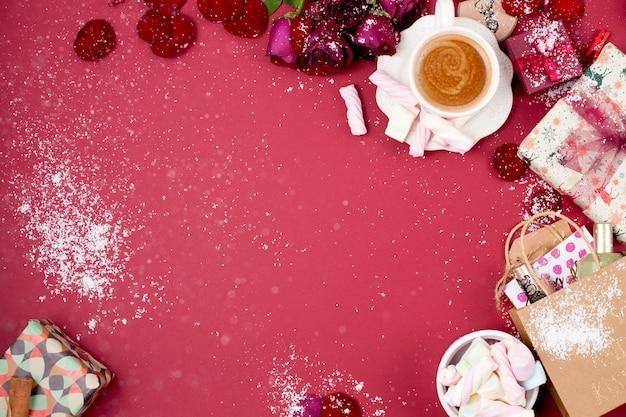 Filiżanka aromatycznej kawy i świątecznych dekoracji na czerwonym tle. prezenty i syootrizy na boże narodzenie. widok z góry. rama. skopiuj miejsce