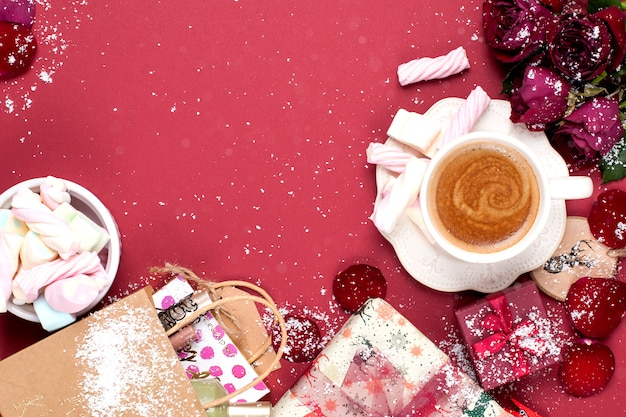 Filiżanka aromatycznej kawy i świątecznych dekoracji na czerwonym tle. róże, prezenty i świąteczne niespodzianki. widok z góry. rama. kopiowanie spase