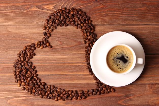 Filiżanka aromatycznej kawy i ziaren kawy na drewnianym tle