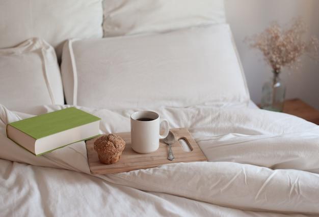 Filiżanka aromatycznej książki z kawą i świeca na łóżku z miękkim kocem w pomieszczeniu