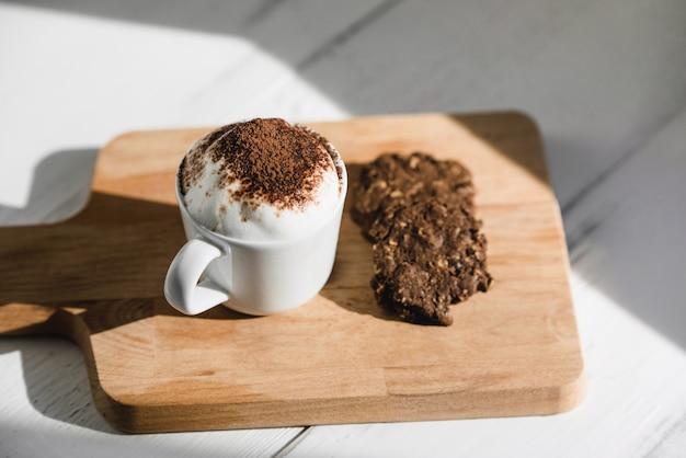 Filiżanka babyccino z ciemnymi czekoladowymi ciasteczkami podawana na drewnianym talerzu w kawiarni