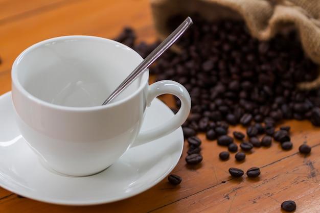 Filiżanka biała kawa i kawowe fasole w worku na drewnianym biurku
