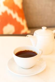 Filiżanka białej herbaty z czajniczkiem na stole