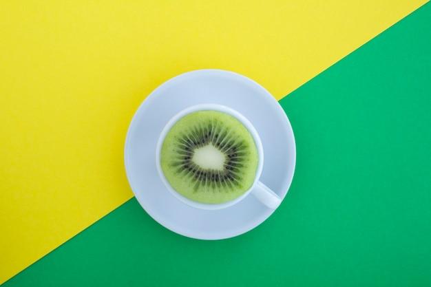 Filiżanka białej herbaty ze świeżego kiwi o połowę na wielokolorowym tle. widok z góry. skopiuj miejsce. kreatywny kolaż żywności.