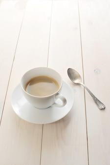 Filiżanka białej kawy i spodek z łyżeczką