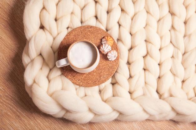 Filiżanka cappuccino i ciasteczka na tle koca z grubej przędzy. atmosfera domowości i komfortu