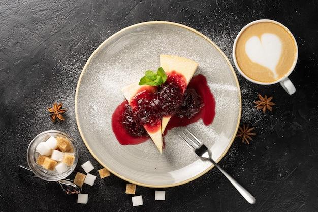 Filiżanka cappuccino i dwa plasterki sernika na okrągłym talerzu skropione dżemem truskawkowym.