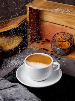 Filiżanka cappuccino i świeczka w drewnianym pudełku na stole
