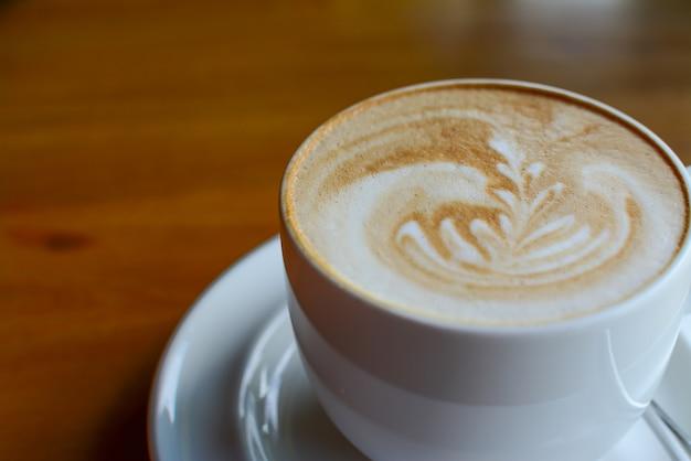 Filiżanka cappuccino kawa z latte sztuką na drewnianym tle serw w kawiarni