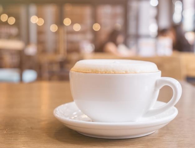 Filiżanka cappuccino kawa z pianką pokrywa pianka na górze. kawiarnia sklepu bokeh światła rocznika tło.