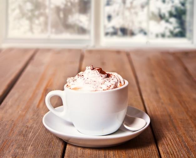 Filiżanka cappuccino na drewnianym stole w pobliżu zamarzniętego okna