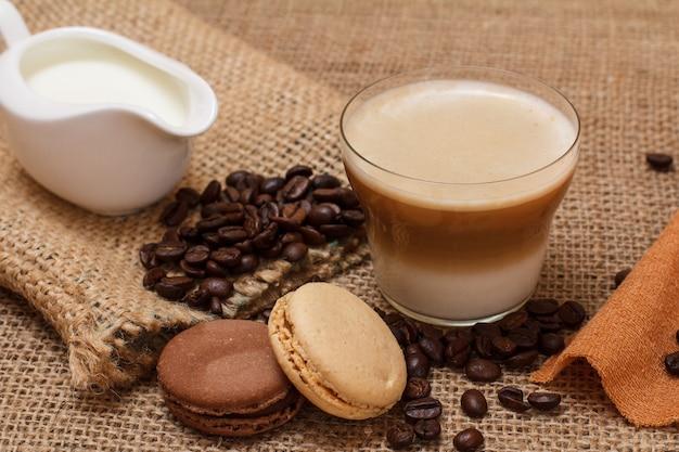 Filiżanka cappuccino, sosjerka ze śmietaną, ziarna kawy, płócienny worek i makaroniki na worze tle. widok z góry.