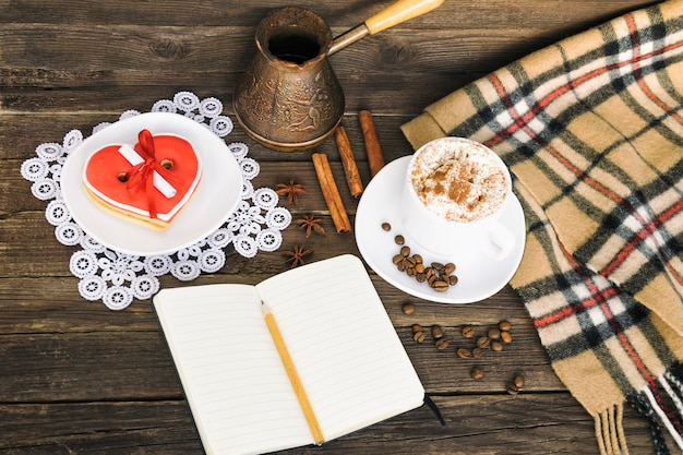 Filiżanka cappuccino, wiadomość szerokość ciasteczka w kształcie serca, notatnik, ołówek i dzbanki do kawy na brązowy drewniany stół