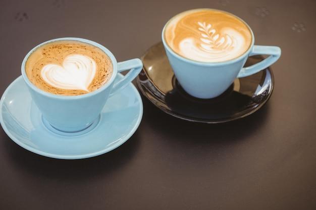 Filiżanka cappuccino z kawową sztuką na drewnianym stole przy sklep z kawą