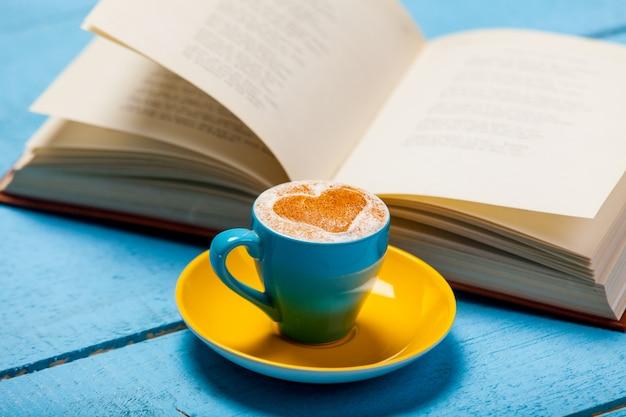 Filiżanka cappuccino z książką na niebieskim drewnianym stole