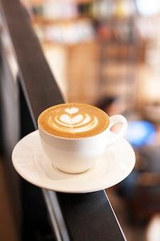Filiżanka cappuccino z latte art stoi na tle kawiarni w rozmyciu. biały ceramiczny kubek i miejsce na tekst.