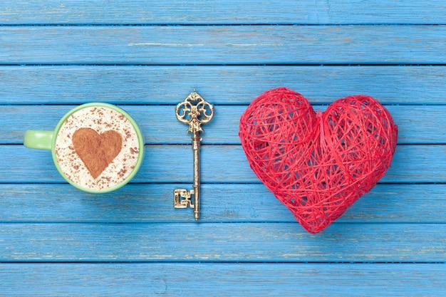 Filiżanka cappuccino z symbolem kształtu serca, kluczem i zabawką na niebieskim drewnianym.