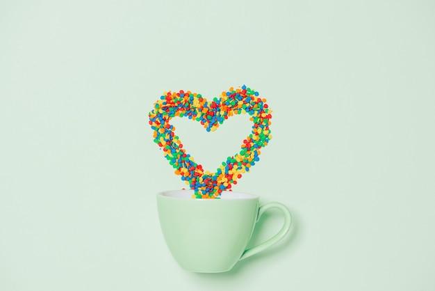 Filiżanka cappuccino z symbolem w kształcie serca i cukierkami na pastelowym zielonym tle