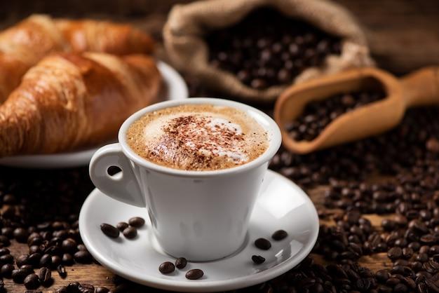 Filiżanka cappuccino z ziaren kawy jako tła z bliska