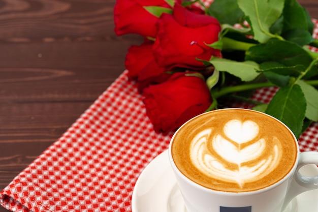 Filiżanka cappucino ze sztuką i bukietem róż na drewnianym stole z bliska