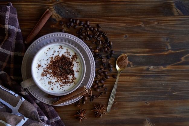 Filiżanka capuccino kawa z cynamonowymi i kawowymi fasolami na drewnianym copyspace