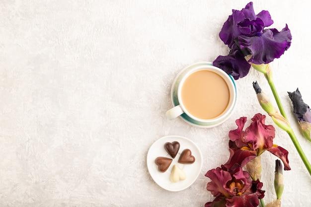 Filiżanka cioffee z cukierkami czekoladowymi i fioletowymi i bordowymi kwiatami tęczówki na szarym tle.