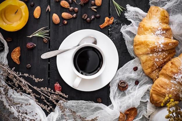 Filiżanka czarna kawa i croissants na czerni powierzchni, odgórny widok. płaskie układanie ziaren kawy espresso i cornetto na ciemnym rustykalnym stole