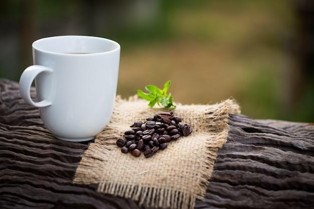 Filiżanka czarna kawa i kawowe fasole na drewnianym tle.