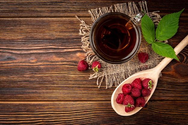 Filiżanka czarnej herbaty i maliny na ciemnym tle drewnianych