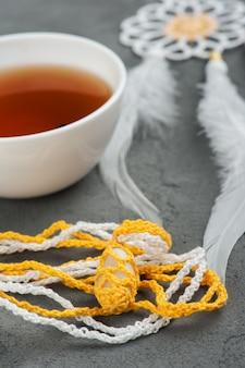 Filiżanka czarnej herbaty i szydełkowane kamyki